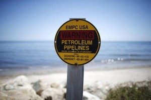 A sign warns of petroleum pipelines next to an oil slick along the coast of Refugio State Beach in Goleta